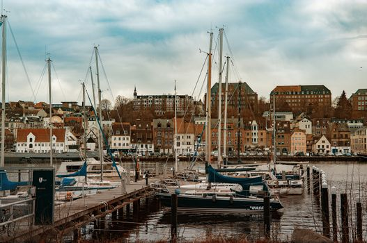 FLENSBURG, GERMANY. JANUARY 28, 2020. Yachts at the pier People walking on the embankment