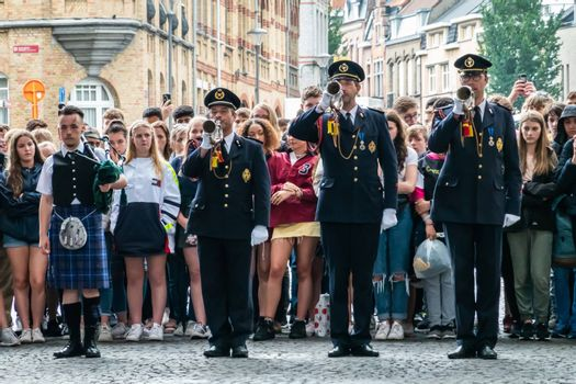 Diksmuide, Flanders, Belgium -  June 19, 2019: Historic Menin Gate. Last Post performance by four men musicians. Rows of English school girls in back.