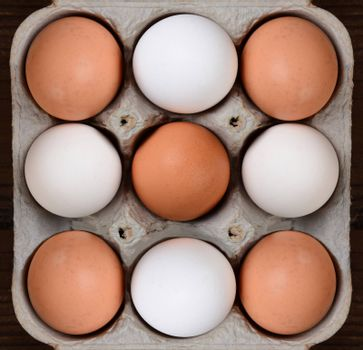 High angle view of a carton of brown and white farm fresh eggs. The nine egg cardboard crate fills the frame with a bit of wood table showing on the sides.