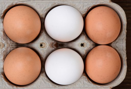 High angle view of a carton of brown and white farm fresh eggs.