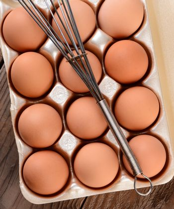 High angle view of a carton of brown eggs with a whisk laying across. The carton is resting on a rustic wooden farmhouse table.