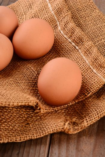 Closeup of 4 brown eggs on a burlap sack.  Vertical format with shallow depth of field.