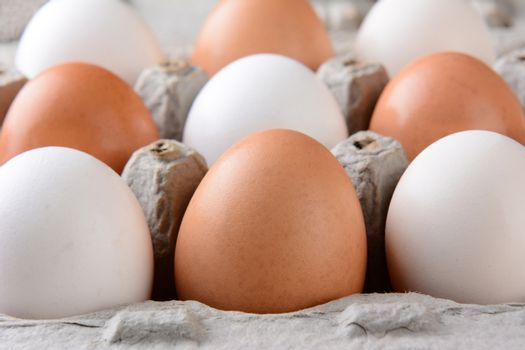 Closeup of a carton of brown and white eggs with shallow depth of field.