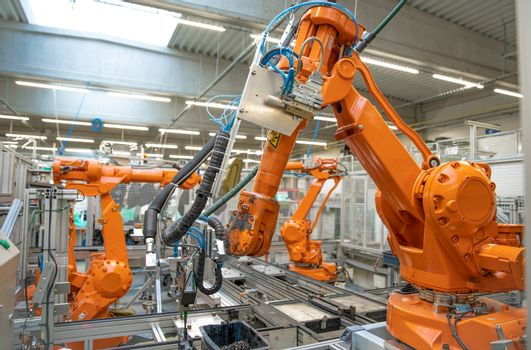 orange robot arms on the production line. controlled by a computer with artificial intelligence