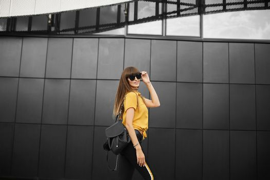 Beautiful brown-haired model girl in the yellow sleeveless shirt and in the fashionable sunglasses with trendy backpack smiles and posing outdoors at urban background