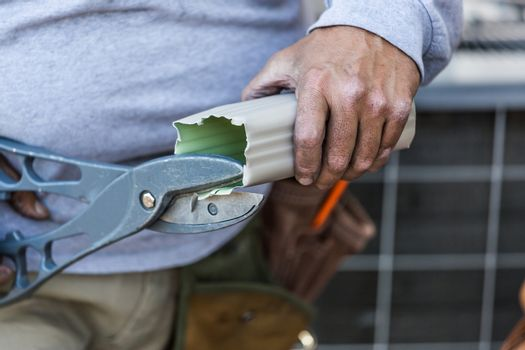 Worker Cutting Aluminum Rain Gutter With Heavy Shears.