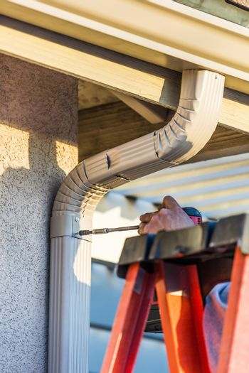 Worker Attaching Aluminum Rain Gutter and Down Spout to Fascia of House.