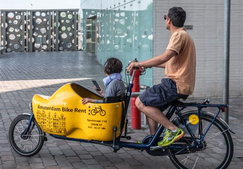 Bakfiets or front-trunk bike on the move in Amsterdam Netherland