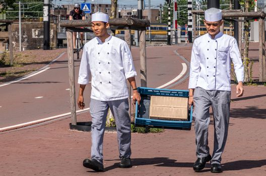 Two kitchen helpers carry crate, Amsterdam Netherlands.