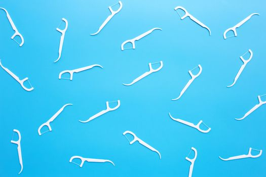 White floss toothpicks on blue background. Top view