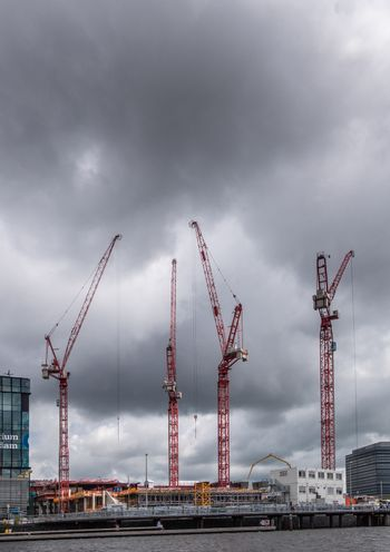 Construction site with tall red cranes on Oosterdocskade in Amst