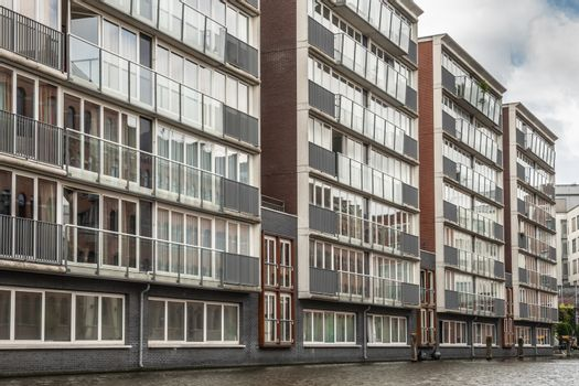 Modern apartment buildings along canal in Amsterdam, the Netherl