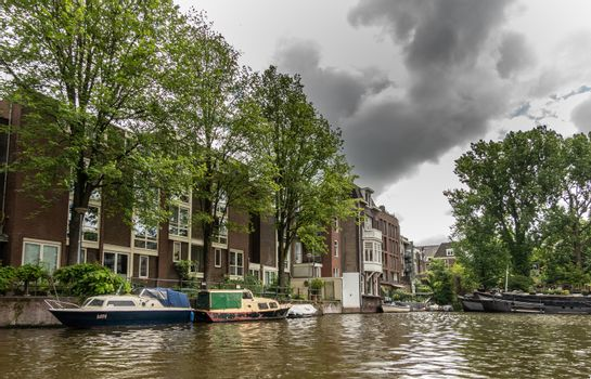 Canal view with green trees and boat under heavy cloudscape in A