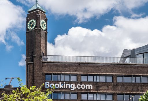 Booking.con dark stone building with clock tower in Amsterdam, t
