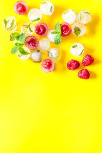 Berries and mint in ice cubes top view.