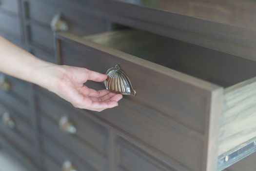 Hand opening brown wooden filing cabinets drawers.