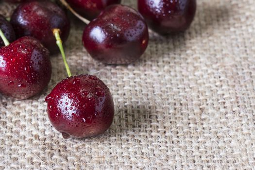 Red cherry with water drop on the sackcloth