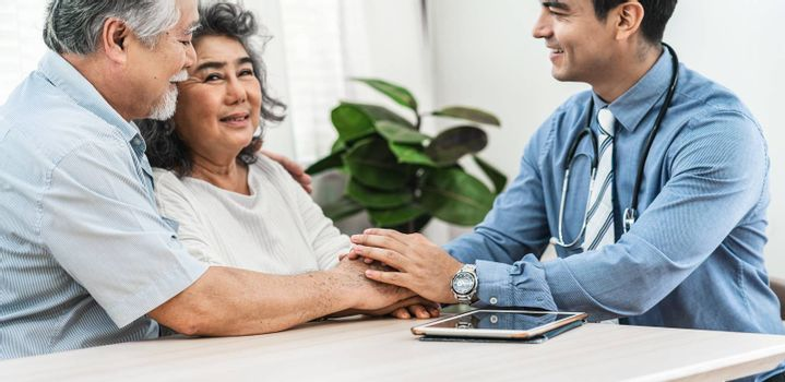 Closeup Doctor hands holding Asian grandparent patient in house for encourage, service Life insurance at home,healthcare with Long live and Elderly society,Prevent epidemic and Covid19 Disease concept