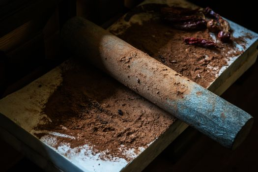 Grinding cacao beans with chili peppers to make chocolate by stone rolling pin on stone surface. hand made chocolate.