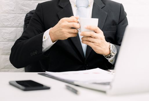 Coffee break businessman executive working relax on laptop at his desk.