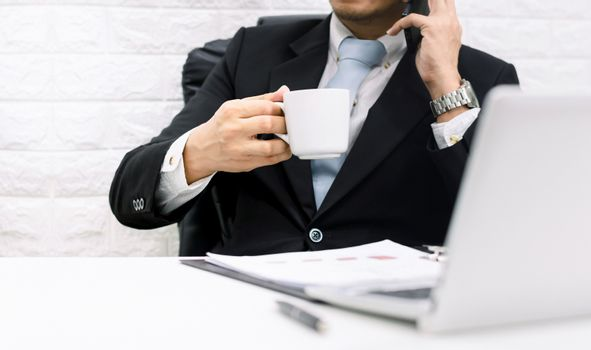 Coffee break businessman executive working relax Hold the phone on laptop at his desk.