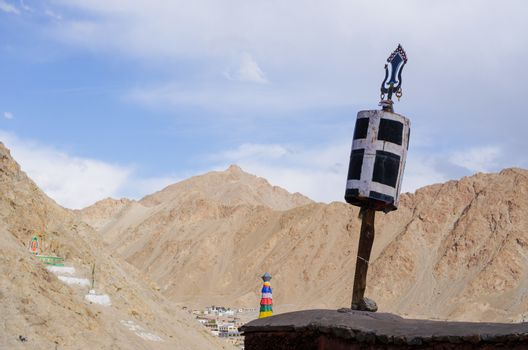 A Buddhist prayer wheel in front of the dry landscape of the Him
