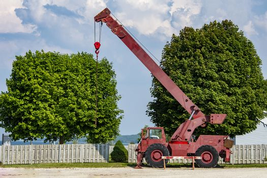 An old red car with a raised boom, a crane stands behind the fence waiting for a major overhaul