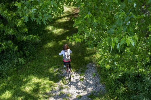 A girl with a backpack rides a red bike along a path among the trees