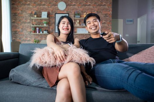Asian couple is watching TV on the sofa at home on a holiday and smiling and laughing happy.