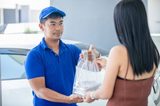 Asian delivery servicemen wearing a blue uniform with a blue cap and handling food boxes in plastic bags to give to the customer in front of the house. Online shopping and Express delivery
