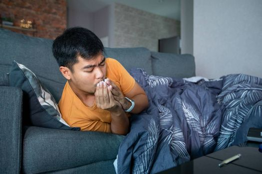 Asian man is ill and coughs on the sofa at home and he uses a thermometer to check the temperature during the coronavirus epidemic.
