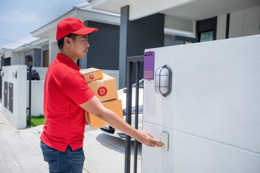 Asian delivery servicemen wearing a red uniform with a red cap handling cardboard boxes to give to the customer in front of the house and Click the doorbell. Online shopping and Express delivery