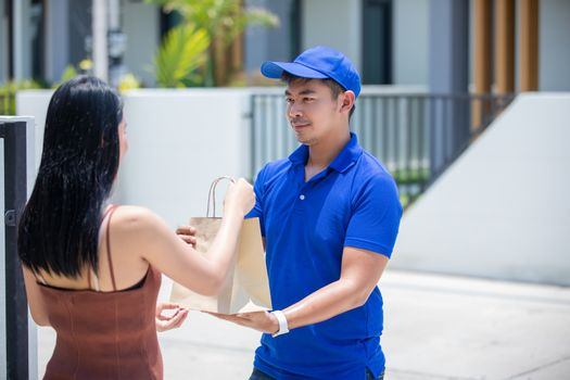 Asian delivery servicemen wearing a blue uniform with a bluecap and  handling cardboard boxes to give to the female customer in front of the house. Online shopping and Express delivery
