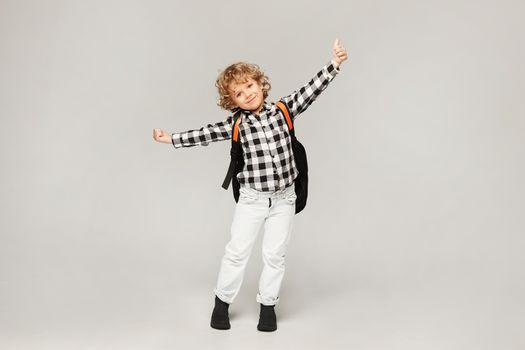 A little schoolboy is happy to start the school year. Happy kid with a backpack posing at the white background, isolated