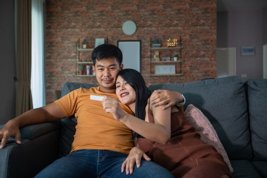 Happy Asian couple smiling looking cheerful after a home pregnancy test in sofa at home