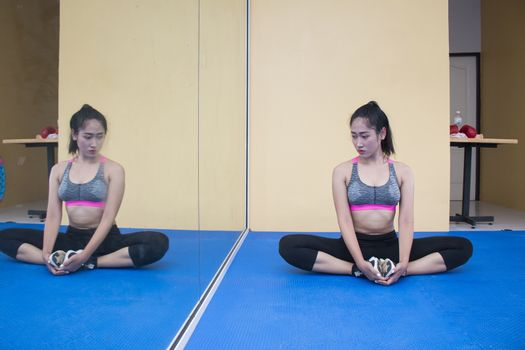 Health concept. Young attractive woman does yoga exercise in the gym against  mirror