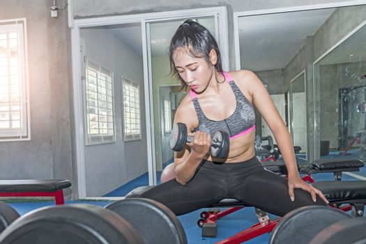 Young asian woman holding dumbbells in gym.Sport women