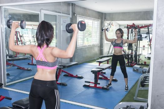 woman exercising with dumbells at the gym in front of a mirror.