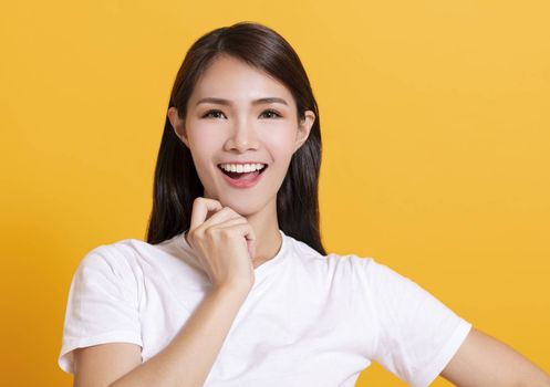 smiling young asian woman  with yellow background