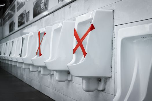 White ceramic urinals in men public toilet. Social distancing in men restroom to prevent coronavirus pandemic. Man bladder health with urinary incontinence problem. Urine infections. Male latrine WC.