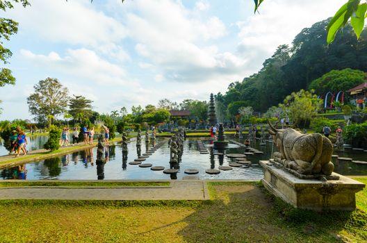 Tirtagangga, Indonesia - 28 Aug 2014: Tourists flock the Tirtagangga temple gardens, its stone causeway and fountains, in Bali, Indonesia