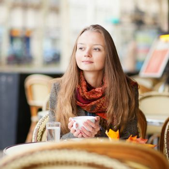 Pensive girl in a Parisian outdoor cafe