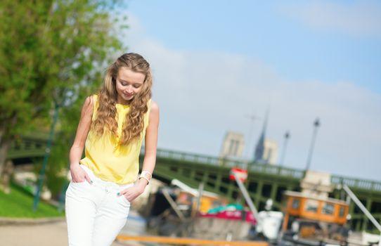 Girl walking on a Parisian embankment