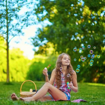 Young girl sitting on the grass and blowing bubbles on a summer day