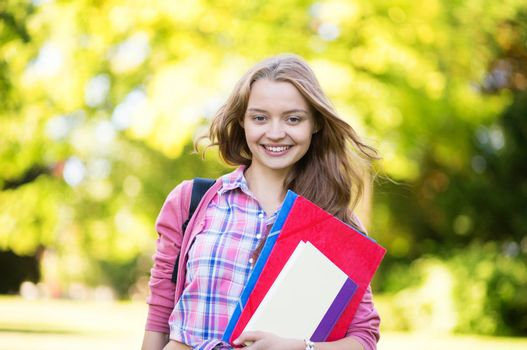 Student girl outdoors going back to school and smiling