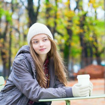 Young Parisian girl drinking coffee in the Luxembourg garden on a fall day