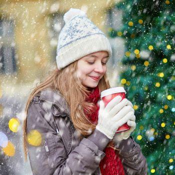 Girl drinking take away coffee, hot chocolate or eggnog near decorated Christmas tree during snowfall
