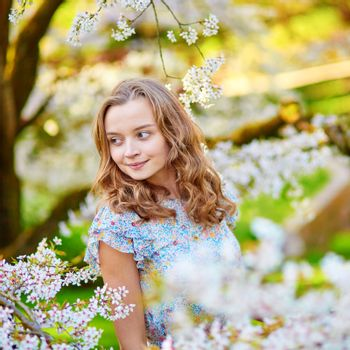 Beautiful young woman in cherry blossom garden on a spring day