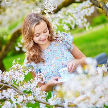 Beautiful young woman in cherry blossom garden with cup of tea or coffee on a spring day