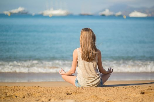 Beautiful young woman meditating on the beach